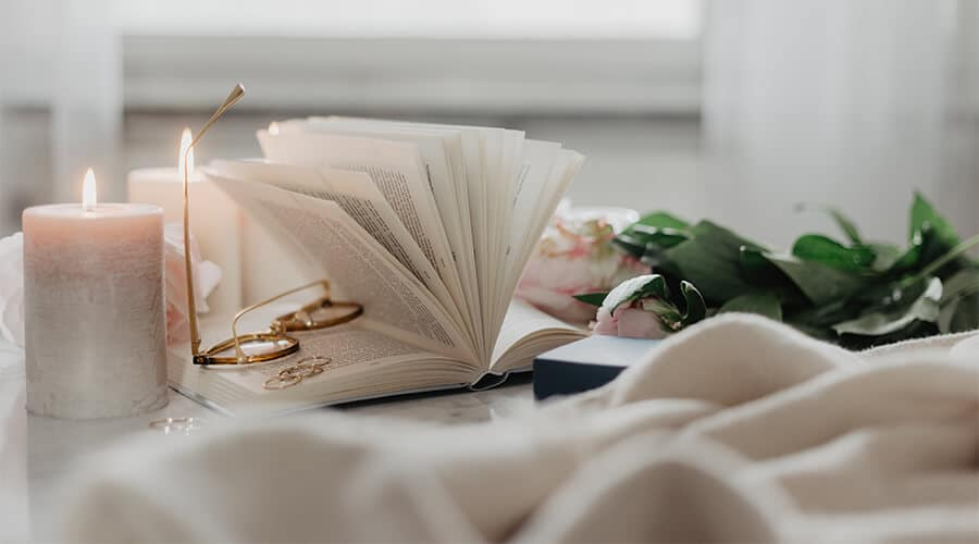Hygge image with candles, a book and a throw